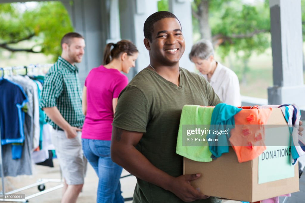 Man holding box of clothes donations at a donation center : Stock Photo