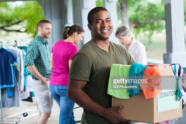 man holding box of clothes donations at a donation center - donation stock photos and pictures