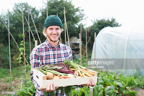 Man holding box of vegetables on allotment.