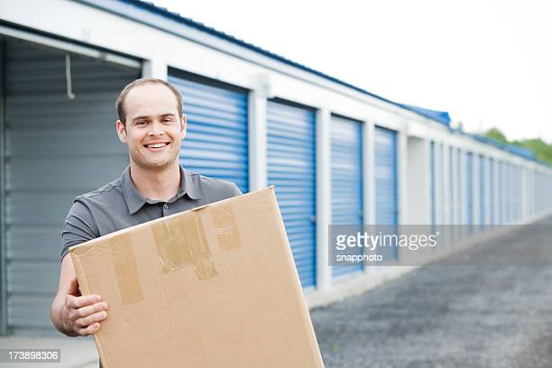 man holding box outside self storage unit - storage compartment stock pictures, royalty-free photos & images