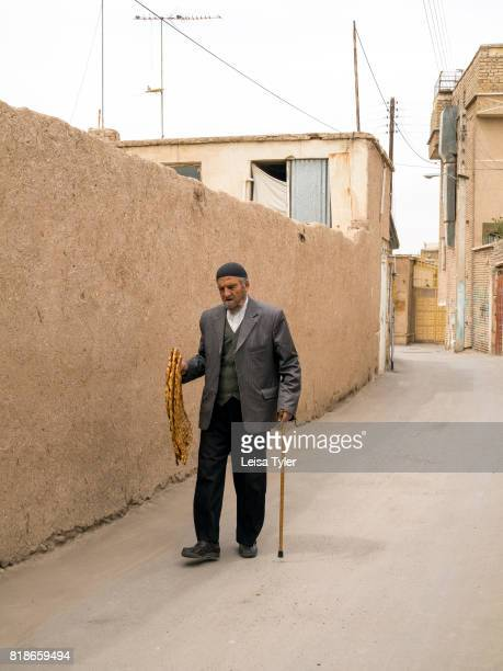 OLD CITY KASHAN ISFAHAN IRAN A man holding bread walking in the back streets of Kashan Iran One of the oldest inhabited cities in Iran Kashan dates...