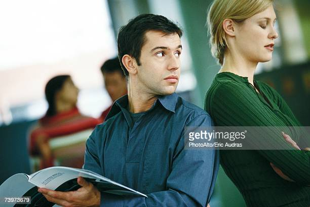 Man holding brochure, looking over shoulder at female colleague turning her back to him