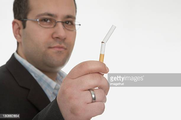 man holding broken cigarette: smoking cessation - smoking crack stock photos and pictures