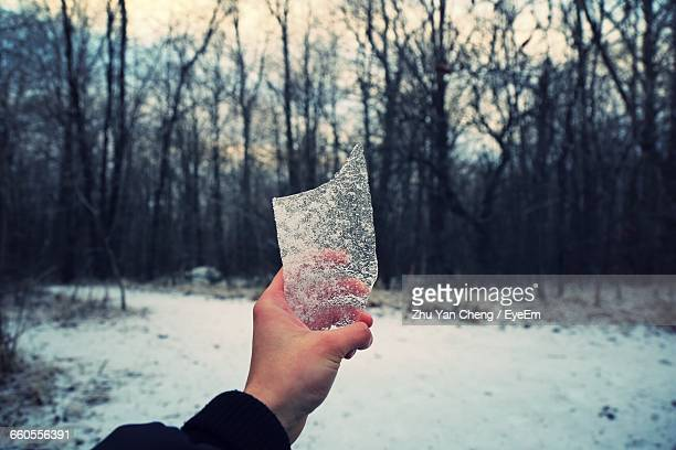 Man Holding Broken Piece Of Glass In Snowy Forest