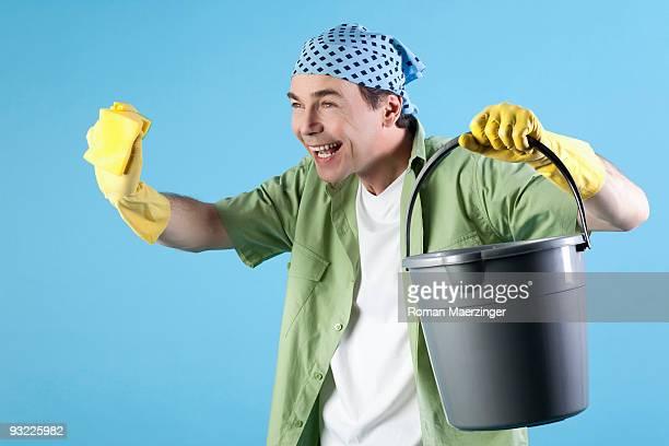 Man holding bucket and sponge, smiling, portrait