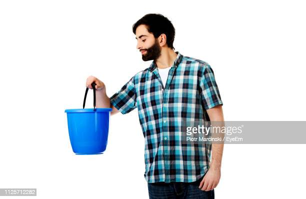 man holding bucket while standing against white background - バケツ ストックフォトと画像