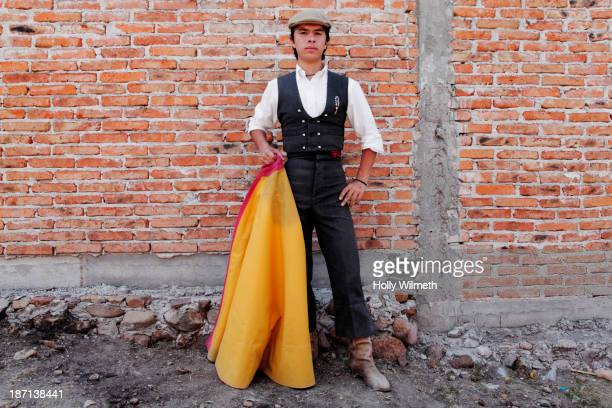 man holding bullfighting cape in front of brick wall - bullfight stock pictures, royalty-free photos & images