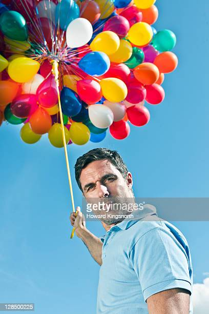 man holding bunch of balloons, close up