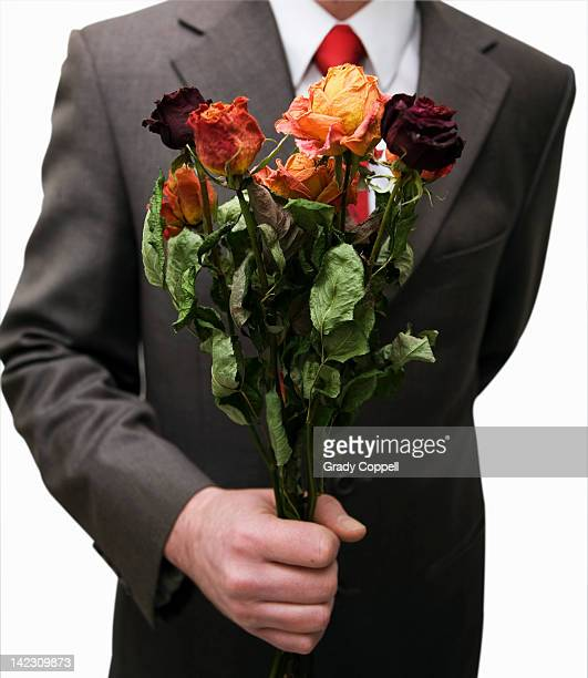 Man holding bunch of dead flowers
