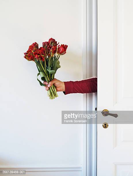 Man holding bunch of red roses from behind door