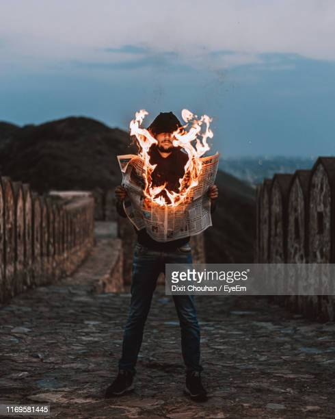 man holding burning newspaper while standing outdoors during sunset - burning stock pictures, royalty-free photos & images