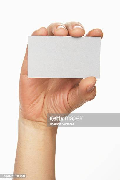 Man holding business card, close-up (focus on card)