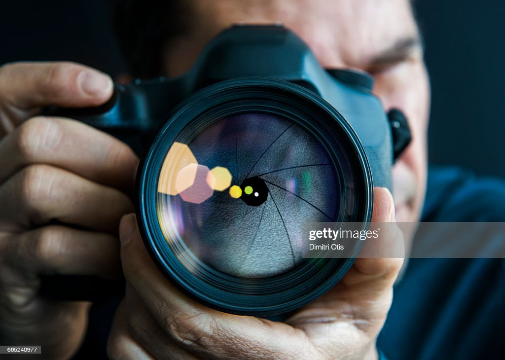 Man holding camer, close-up of lens : Stock Photo