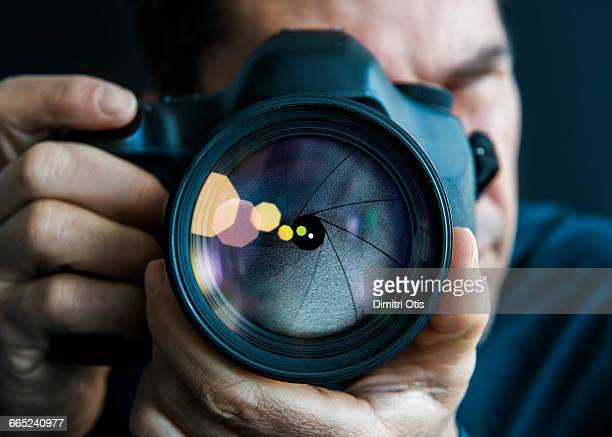 man holding camer, close-up of lens - photographer stock photos and pictures