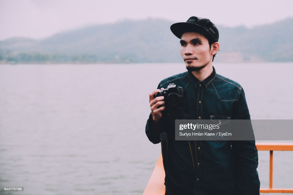 Man Holding Camera By Lake : Stock Photo
