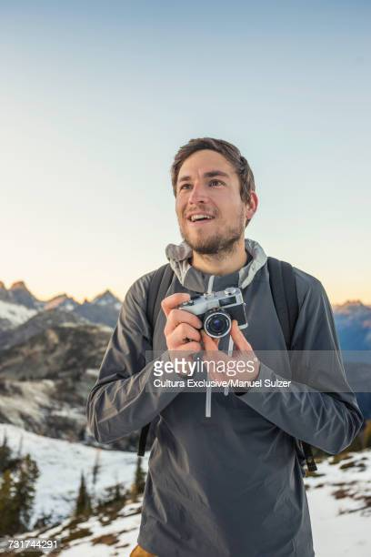 Man holding camera in North Cascades mountain range, Washington State, USA