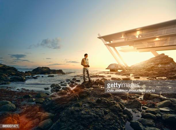 Man holding camera on rocks near modern waterfront architecture