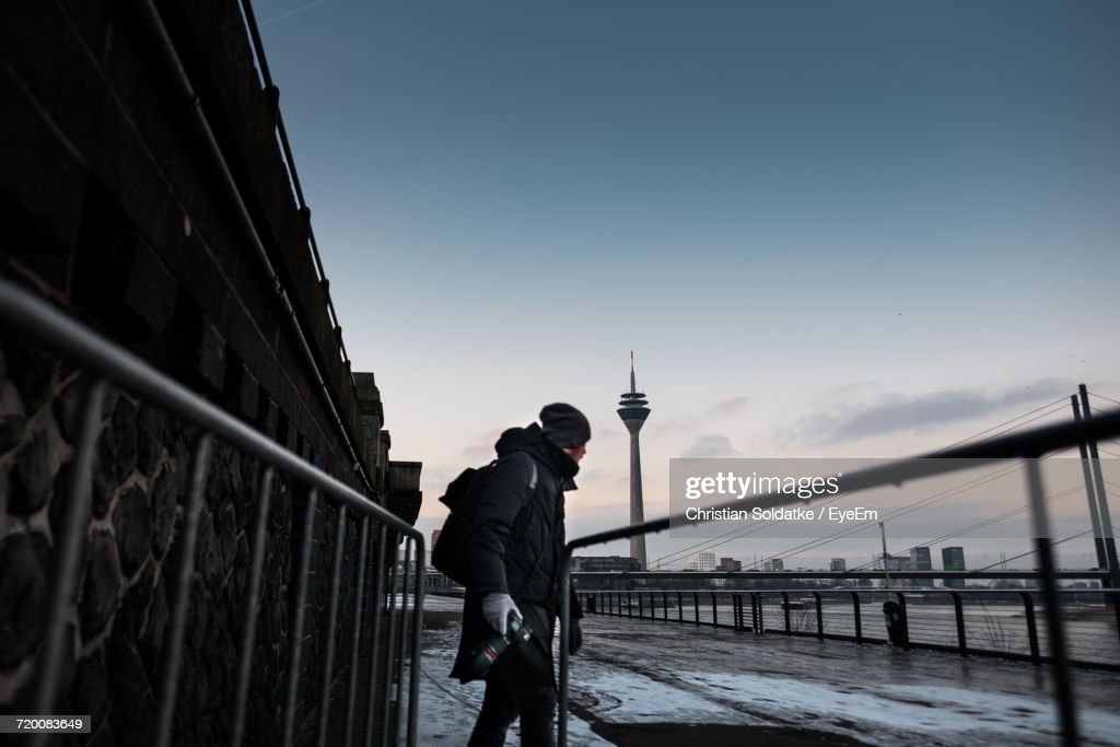 Man Holding Camera Standing On Promenade Against Rheinturm Tower During Winter : Stock Photo