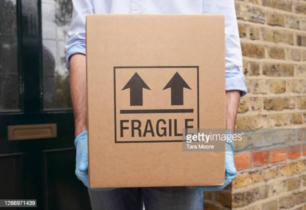 man holding cardboard box with protective gloves - fragile sign stock pictures, royalty-free photos & images