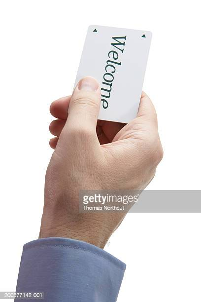 Man holding cardkey with 'Welcome' across front, close-up of hand