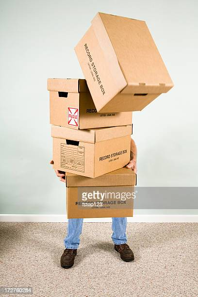 Man holding, carrying many cardboard boxes. Falling from stack.