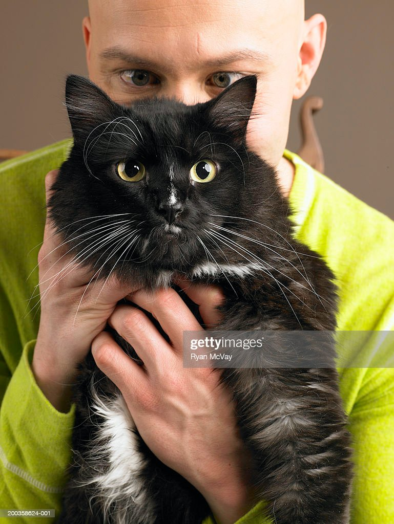 Man holding cat in front of face : Stock Photo