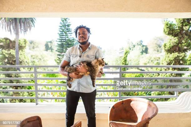 Man holding cat on porch.