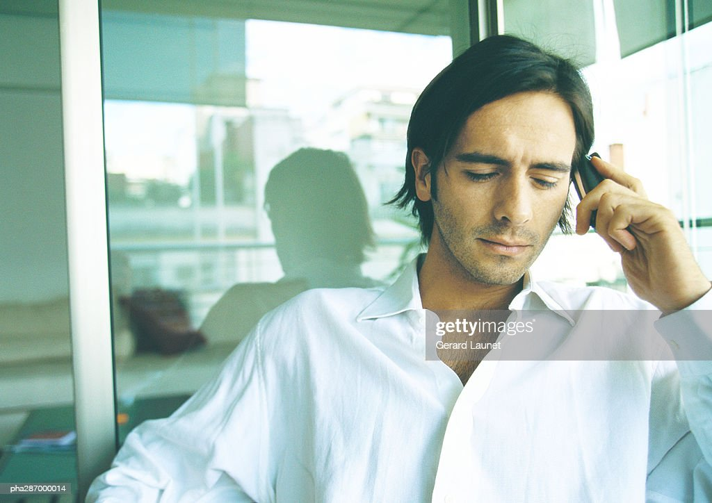 Man holding cell phone to ear, eyes lowered : Stockfoto