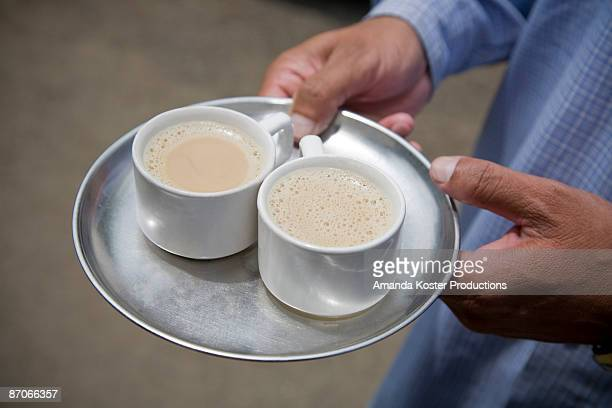 Man holding chai tea on a steel patter.