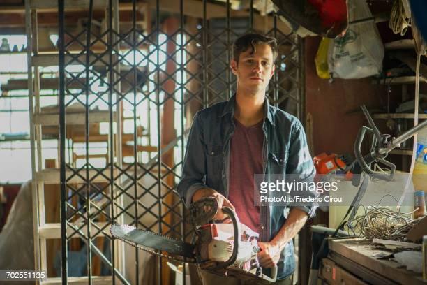 man holding chainsaw in workshop, portrait - lagerhaltung stock-fotos und bilder