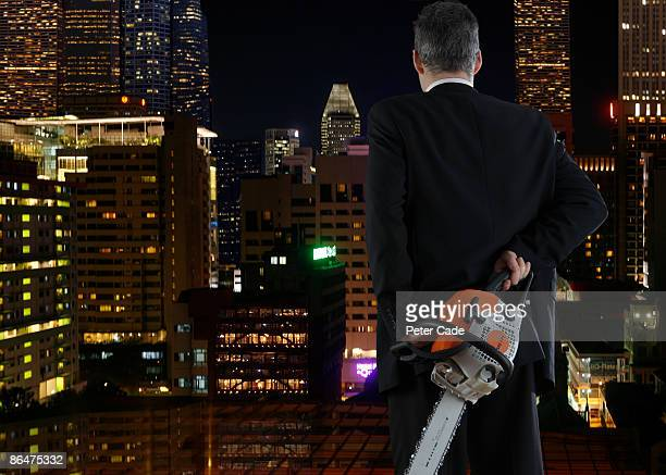 Man holding chainsaw looking out over city