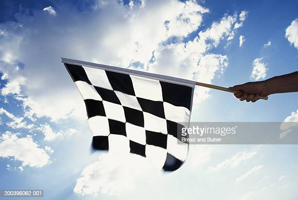 Man holding checkered flag at racetrack, close-up