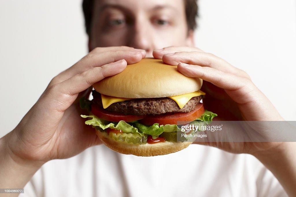 Man holding cheeseburger : Stock Photo