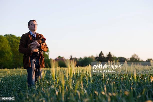 man holding chicken
