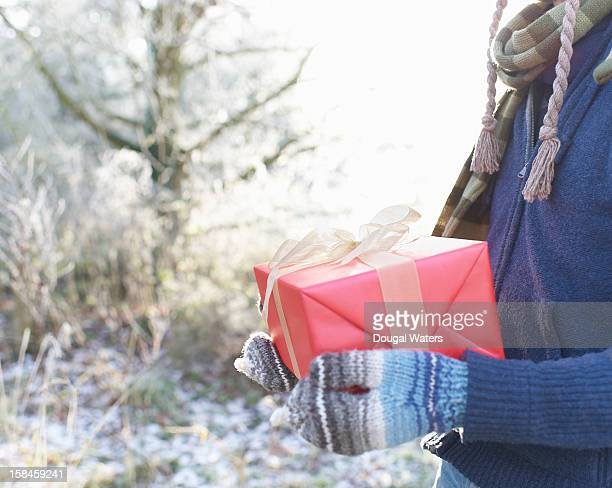 Man holding Christmas present in Winter setting.