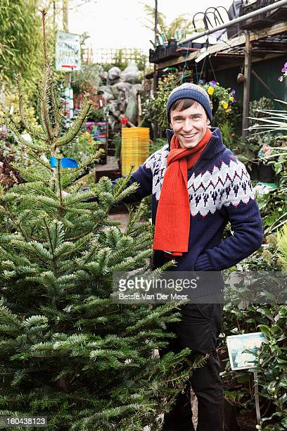 Man holding Christmas tree in garden centre.