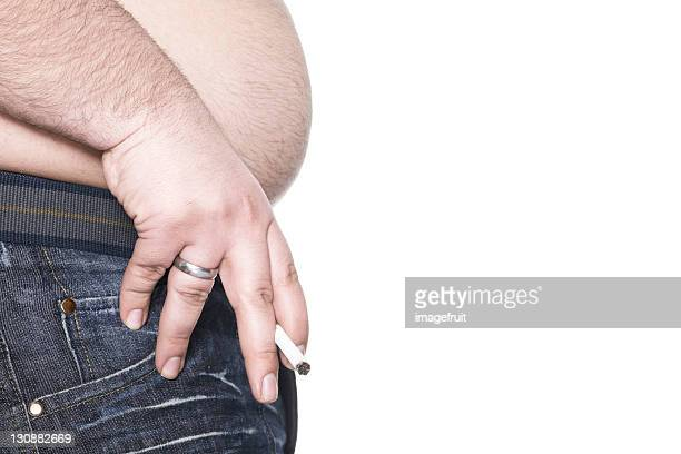 Man holding cigarette between two fingers, presenting his beer belly