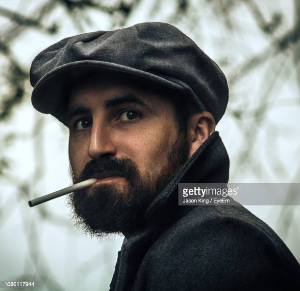 man holding cigarette in mouth - flat cap stock pictures, royalty-free photos & images