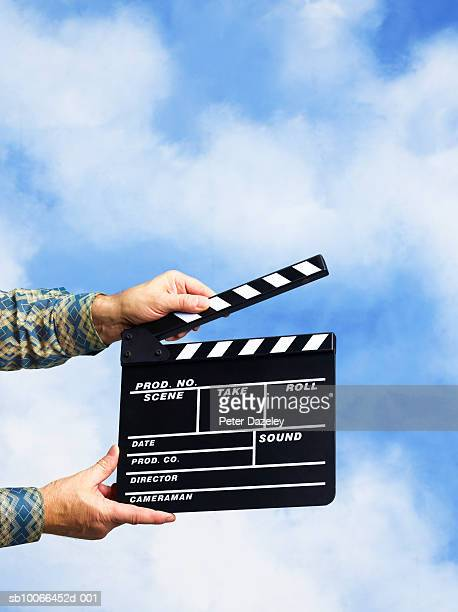 Man holding clapperboard against sky backdrop