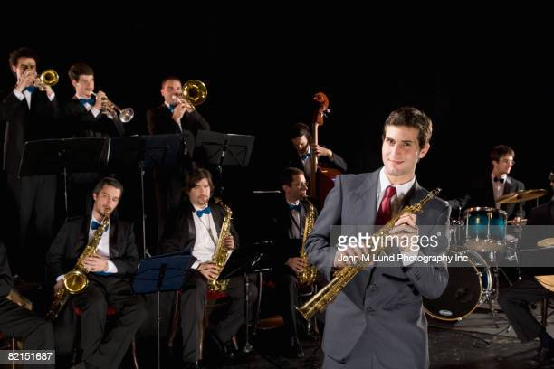 man holding clarinet in front of orchestra - soloist stock photos and pictures