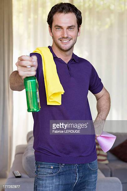 Man holding cleaning equipment and smiling
