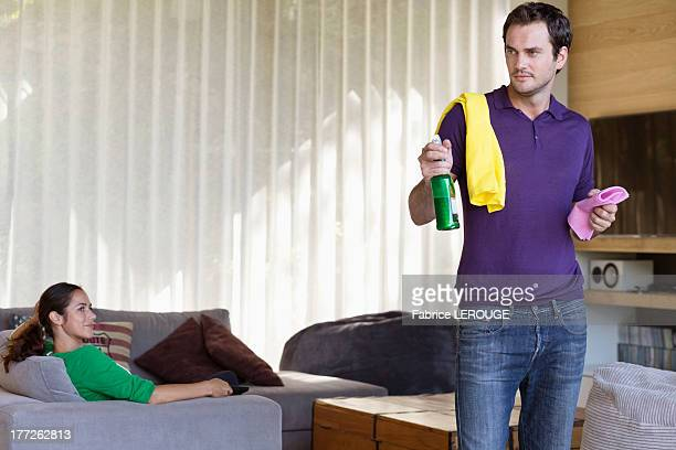 Man holding cleaning equipment with his wife sitting on a couch