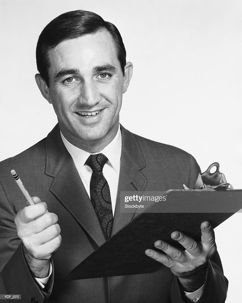 Man holding clipboard and pencil : Stock Photo