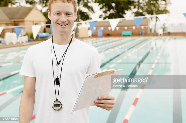 Man holding clipboard by swimming pool