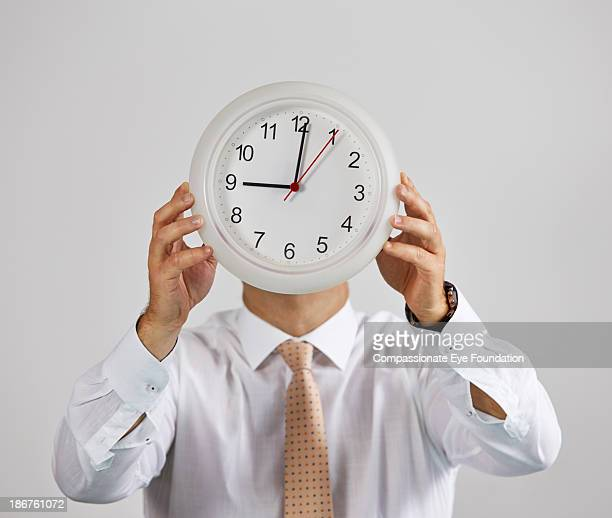 Man holding clock in front of face