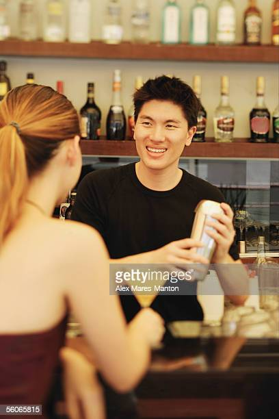 Man holding cocktail mixer, woman in front of him