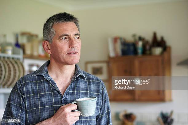 Man holding coffee cup in kitchen
