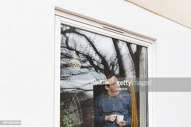 Man holding coffee cup looking through window while standing in house