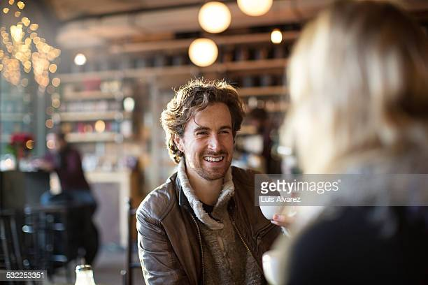 Man holding coffee cup while looking at woman