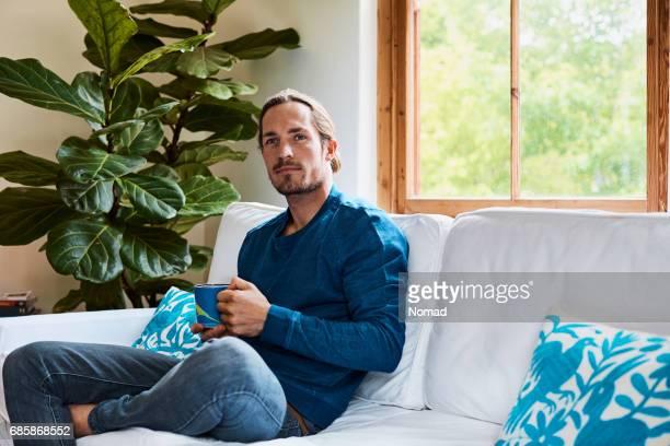 家庭でよそ見しながらコーヒー カップを保持している男 - 長袖 ストックフォトと画像
